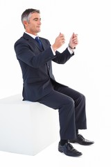Businessman sitting on a cube with arms out