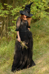 woman in black dress and witch's hat, weeds in hands