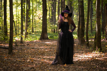 woman in witch's hat holding broom and looking at camera