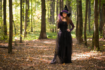 woman in witch's hat smiling and looking at camera