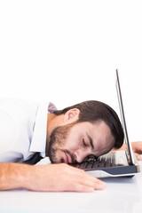 Businessman resting head on laptop keyboard