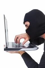 Focused burglar with balaclava typing on laptop