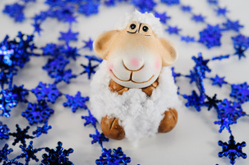 toy sheep on a blue background with snowflakes