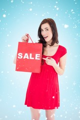 Stylish brunette in red dress showing sale bag