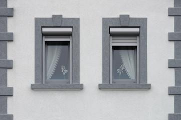 Zwei graue PVC Fenster mit außen liegenden Rollladenkästen