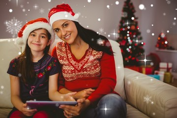 Composite image of festive mother and daughter using tablet