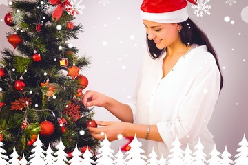 Composite image of woman hanging christmas decorations on tree