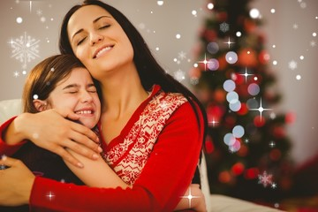 Composite image of festive mother and daughter hugging on couch