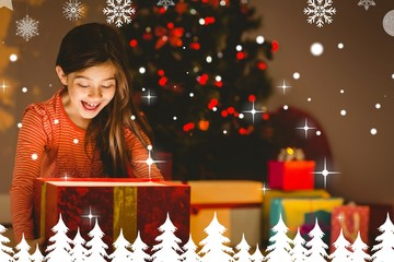 Composite image of little girl opening a glowing christmas gift
