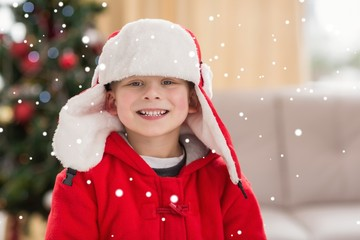 Composite image of festive little boy smiling at camera