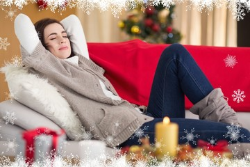 Composite image of brunette napping on the couch at christmas