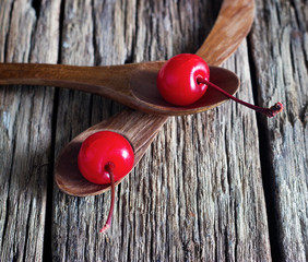 maraschino cherry vibrant on wooden spoon and old table backgrou