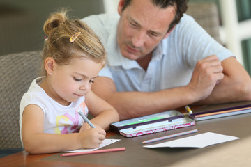 Daddy watching little girl drawing on paper