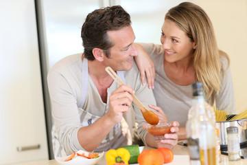 Woman watching husband preparing pasta dish