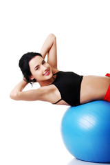 Side view of a woman exercising on fitness ball