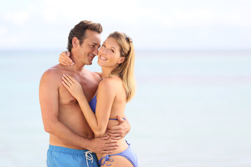 Loving couple in swimsuit embracing at the beach