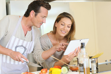 Couple in kitchen looking at pasta dish recipe on tablet