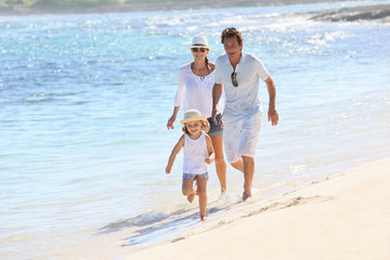 Family running on a white sandy beach