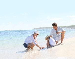 Parents and child playing on a sandy beach together