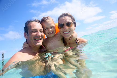 Family enjoying bathing in the sea - 74532139