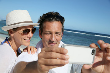 Couple at the beach making a selfy with smartphone