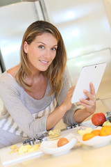 Smiling blond woman looking at recipe on digital tablet