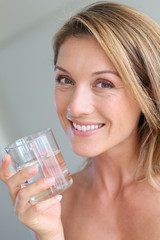 Portrait of blond woman holding glass of water