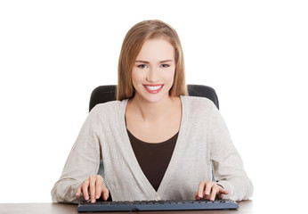 Happy woman typing on a pc keyboard