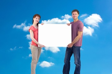 Composite image of couple holding a white sign