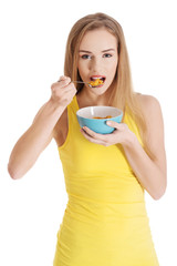 Happy blonde woman eating cereals