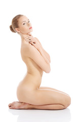 Side view nude woman sitting on her knees
