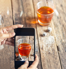 Smartphone take photos of tea and grape on wooden background