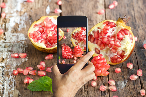 Smartphone take photos of pomegranate on wooden background - 74534116
