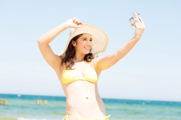 Woman doing selfie on vacation by the ocean
