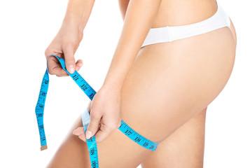 Slim woman measuring her thigh