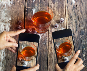 Smartphone take photos of tea and grape on wooden background, vi
