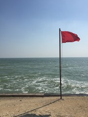 red flag by the sea