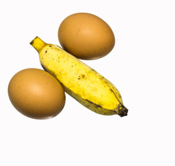 Two eggs and ripe banana composing a penis.