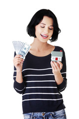 Happy woman holding a house model and dollar bills