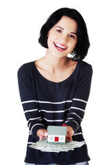 Happy woman holding a house model and polish bills