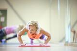 Fototapety Mature woman fitness trainer pushing-up