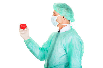 Side view of male doctor holding heart model