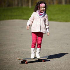 little girl skating on the street