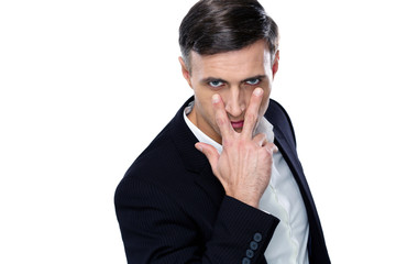 """Confident businessman making """"watching you"""" gesture"""