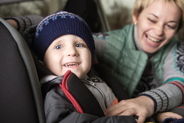 little boy in a a car seat, family in the car