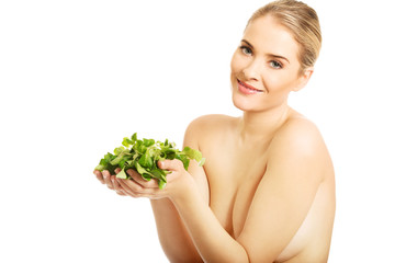 Portrait of happy nude woman holding lettuce