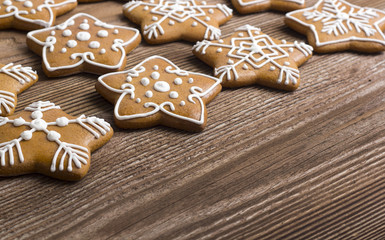 Gingerbread stars with spices on wooden background
