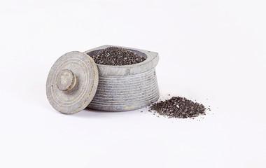 каменная солонка с черной солью на белом фоне