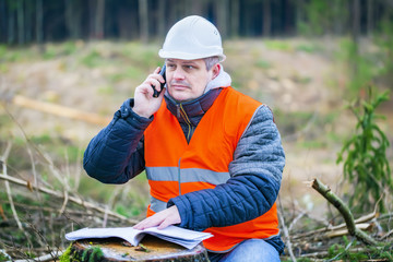Forest engineer talking on a cell phone in the forest