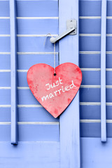 Just Married sign hanging on a closed wood window